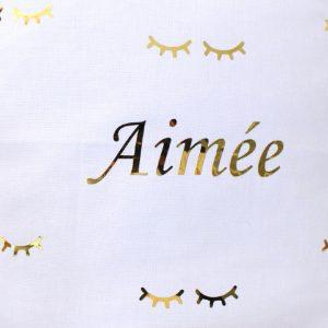 Coussin cils dorés personnalisé avec un prénom